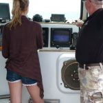 tour guest at the helm of lobster tour boat supervised by captain