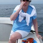 woman eating lobster onboard lobster tour boat