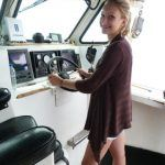 tour guest at the helm of lobster tour boat