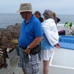 people on lobster tour next to lobster traps